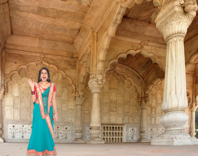 Indian woman in ethnic wear standing in front of elaborate arches and pillars